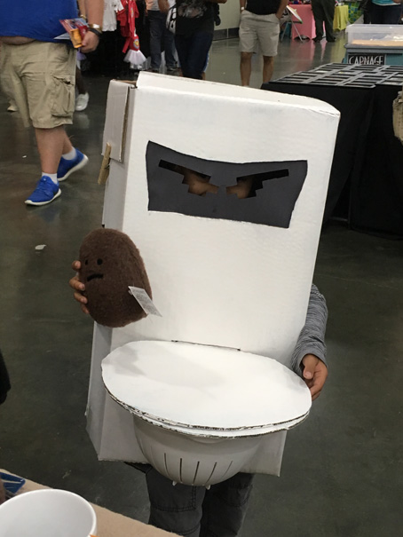 Kid dressed as a toilet holding a poop